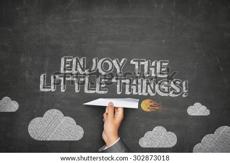 Enjoy the little things concept on black blackboard with businessman hand holding paper plane - stock photo
