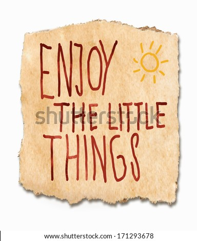 Enjoy the lttle things, an inspirational saying handwritten on a torn fragment of textured, grunge, paper with a sunburst in the corner - grab life with both hands and live it to the full - stock photo