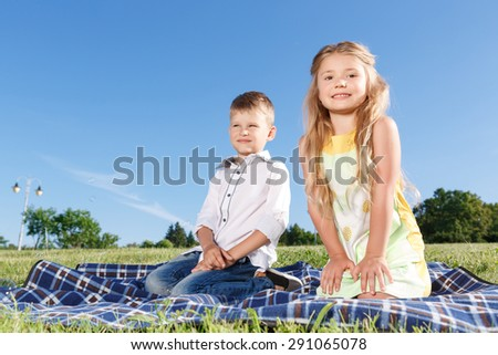 Enjoy the moment. Nice little children holding their  hands down and sitting on  blanket while evincing positive emotions. - stock photo