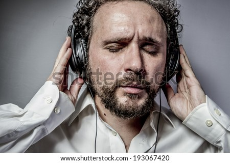 enjoy the music, man with intense expression, white shirt - stock photo