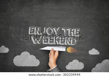 Enjoy the weekend concept on black blackboard with businessman hand holding paper plane - stock photo