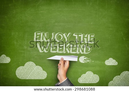 Enjoy the weekend concept on green blackboard with businessman hand holding paper plane - stock photo