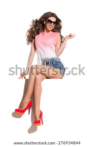 Enjoy the Wind and The Sunlight. Smiling sexy woman in sunglasses, pink top, jeans shorts and red high heels sitting on the white banner. Full length studio shot isolated on white. - stock photo