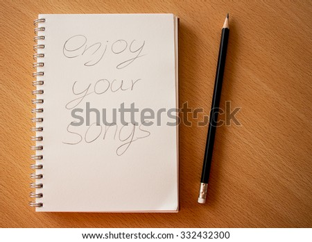 Enjoy your songs word on notebook page. conceptual image for advertising.