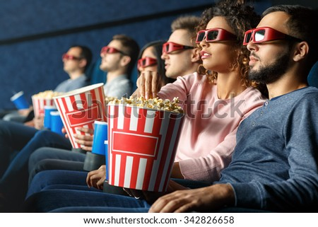 Enjoying a great movie. Shot of a group of friends watching a movie eating popcorn drinking beverages