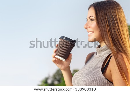 Enjoying a pleasant day. Close up portrait of a profile of a beautiful smiling woman with coffee in her hand   - stock photo