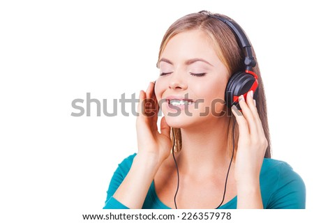 Enjoying an excellent sounds! Cheerful young women holding hands on headphones and smiling while standing against white background