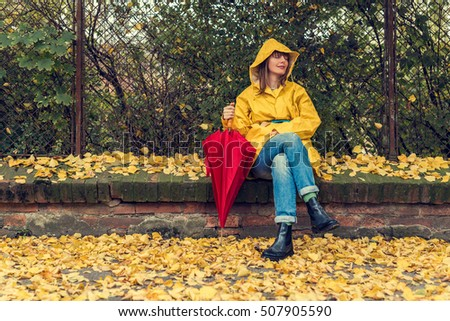 Enjoying autumn days. Woman in yellow raincoat walking down the street