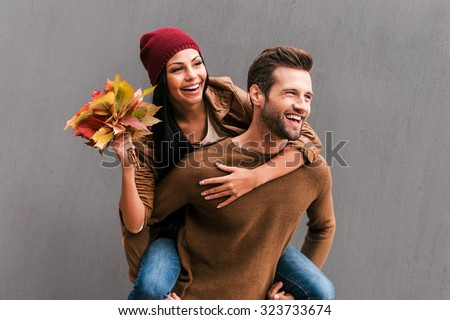 Enjoying autumn time together. Handsome young man piggybacking his girlfriend holding bouquet of orange fallen leaves with grey wall as background  - stock photo