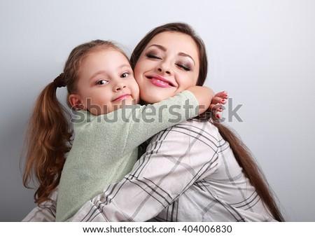 Enjoying beautiful mother cuddling emotional cute kid girl in studio on blue background - stock photo