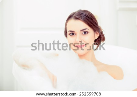 Enjoying bubble bath. Closeup image of attractive young woman in soap foam and smiling while enjoying luxurious bath - stock photo