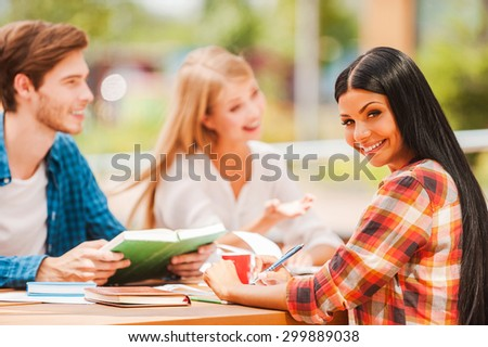 Enjoying campus life. Cheerful young woman holding pen and looking at camera while sitting with her friends at the wooden desk outdoors - stock photo