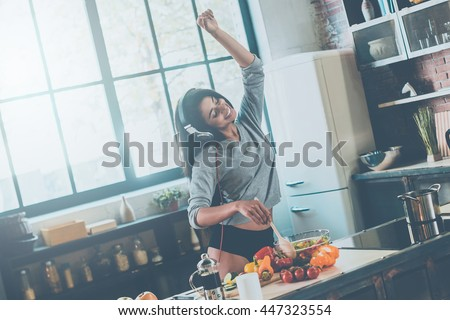 Enjoying carefree morning. Beautiful young mixed race woman in headphones cooking salad and dancing while standing in kitchen at home - stock photo
