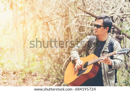 Enjoying carefree time . Happy young man playing the guitar while standing outdoors and enjoy nature