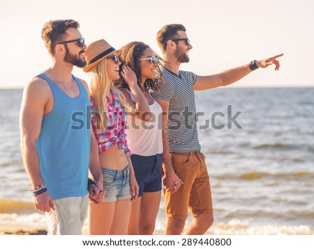 Enjoying carefree time with friends. Group of young cheerful people walking together along the beach and smiling while one man pointing  - stock photo