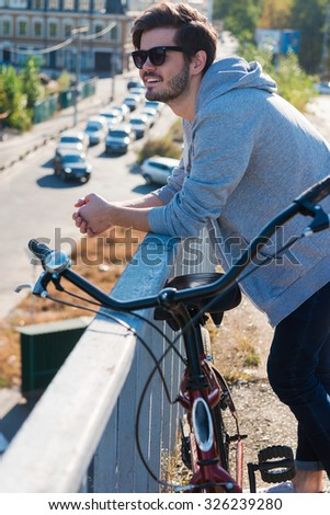 Enjoying city life. Handsome young man standing near his bicycle and looking away while enjoying a cityscape from the bridge  - stock photo