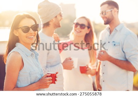 Enjoying coffee break. Beautiful young woman holding coffee cup and smiling while standing near her friends on the roof terrace - stock photo