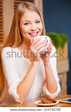 Enjoying coffee break in cafe. Beautiful young smiling woman enjoying coffee in cafe  - stock photo