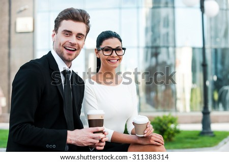 Enjoying coffee break. Two happy young business people holding cups of coffee and looking at camera while sitting outdoors - stock photo