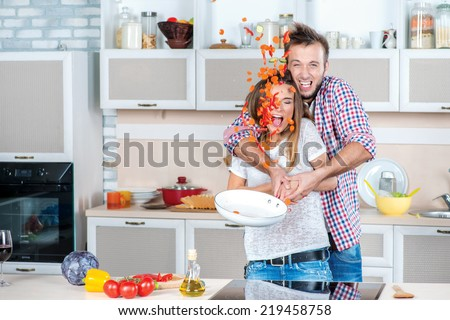 Enjoying cooking together. Young and beautiful couple in love preparing meals in the kitchen and look at each other while standing in the kitchen and throw up the food in the pan - stock photo