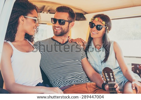 Enjoying every moment of their roadtrip. Three young cheerful friends enjoying time together while sitting inside of the mini van - stock photo