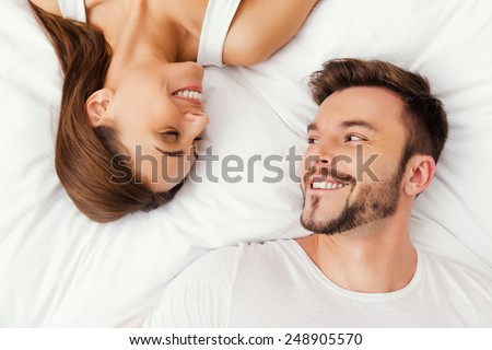 Enjoying every moment together. Top view of beautiful young loving couple lying in bed together and looking at each other - stock photo