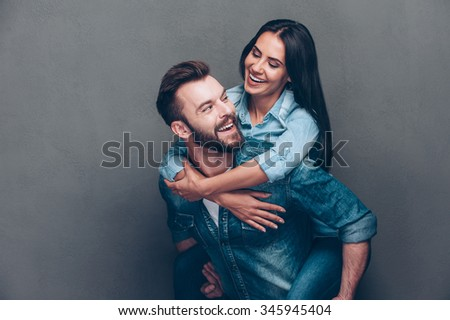 Enjoying every second together. Handsome young man piggybacking beautiful woman and smiling while standing against grey background - stock photo
