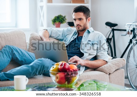 Enjoying free time at home. Handsome young man working on laptop while lying on the couch at home  - stock photo