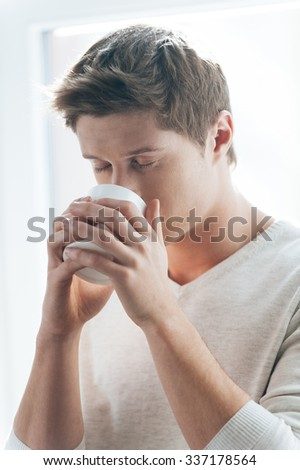 Enjoying fresh coffee. Handsome young man drinking coffee while standing against window - stock photo