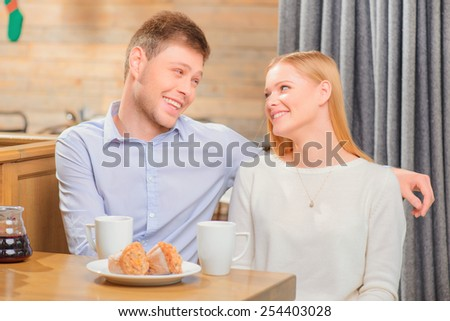 Enjoying fresh coffee together. Beautiful young couple looking at each other and smiling while enjoying coffee in cafe together - stock photo