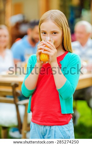 Enjoying fresh juice. Cute little girl drinking orange juice and smiling while her family sitting at the dining table in the background  - stock photo