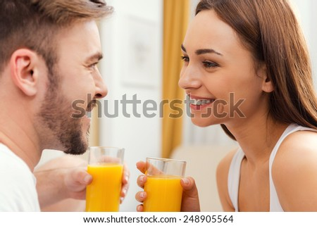 Enjoying fresh juice together. Beautiful young loving couple holding glasses with orange juice and looking at each other with smile  - stock photo