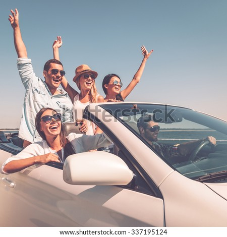 ENjoying friendly trip. Group of young happy people enjoying road trip in their white convertible and raising their arms up - stock photo
