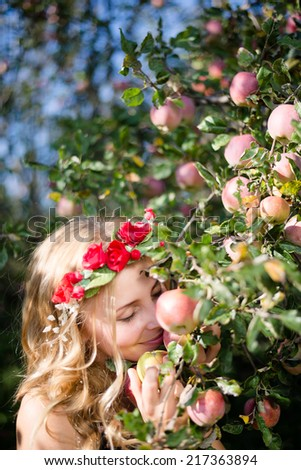 enjoying fruits: portrait of smelling red apples blonde cheerful young pretty lady with wreath of flowers on summer green outdoor copy space background - stock photo