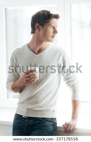 Enjoying good morning. Cheerful young man drinking coffee and looking at camera while standing against window - stock photo