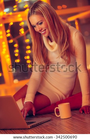 Enjoying good time at home. Beautiful young woman in white sweater and socks working on laptop while sitting on the floor at home with Christmas lights in the background - stock photo