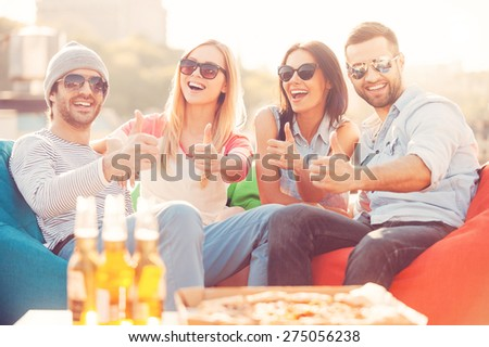 Enjoying good time. Four young cheerful people showing their thumbs up and smiling while sitting on bean bags at the outdoors terrace with pizza and beer laying on foreground - stock photo