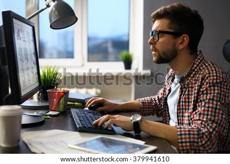 Enjoying good working day. Confident young man working on laptop while sitting at his working place in office