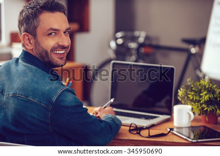 Enjoying good working day. Rear view of confident young man looking over shoulder and smiling while sitting at his working place in office - stock photo