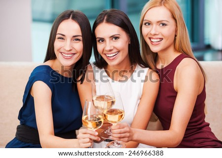 Enjoying great time together. Three beautiful young women in evening gown sitting on the couch and holding glasses with wine  - stock photo