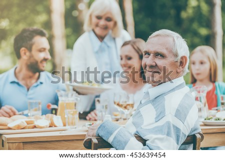 Enjoying great time with family. Happy family of five people sitting at the dining table outdoors while senior man looking over shoulder and smiling - stock photo