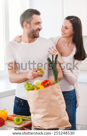 Enjoying happy and healthy life together. Beautiful young couple unpacking shopping bag full of fresh vegetables and smiling while standing in the kitchen together