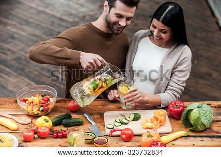 Enjoying healthy food and drinks. Cheerful young man pouring fresh lemonade to his girlfriend while preparing food on the wooden desk together  - stock photo