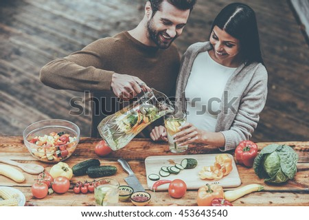 Enjoying healthy lifestyle together. Top view o cheerful young man pouring fresh lemonade to his girlfriend while preparing food on the wooden desk outdoors - stock photo