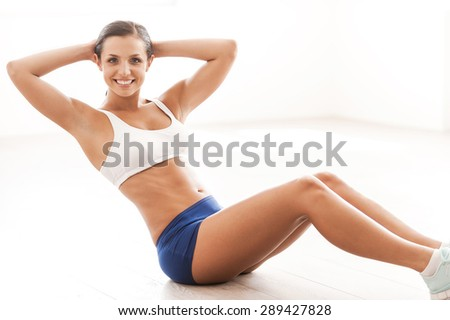 Enjoying her exercising. Beautiful young woman in sports clothing training her abs and smiling while sitting on the floor - stock photo