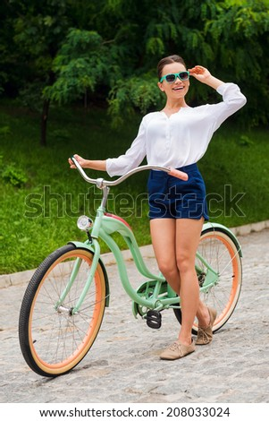 Enjoying her free time at park. Full length of beautiful young smiling woman adjusting her sunglasses while leaning at her vintage bicycle in park - stock photo