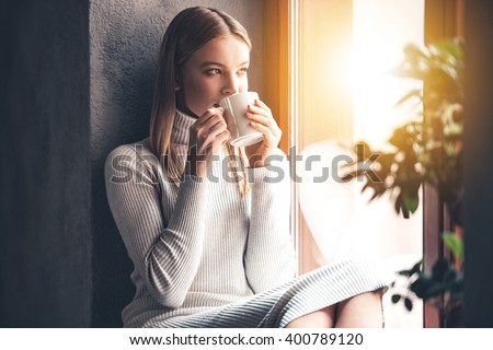 Enjoying her fresh coffee. Beautiful young woman drinking coffee and looking through window while sitting at windowsill at home - stock photo