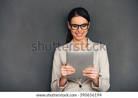 Enjoying her new digital tablet. Beautiful young cheerful businesswoman holding digital tablet and looking at it with smile while standing against grey background - stock photo