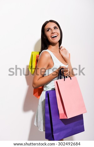 Enjoying her shopping. Excited young woman in dress carrying colorful shopping bags and looking over shoulder with smile while standing against white background  - stock photo