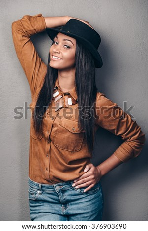 Enjoying her style. Beautiful young cheerful African woman in hat looking at camera and smiling while posing against grey background - stock photo